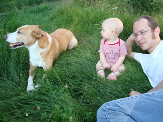 a dog, a baby boy, and a dad in the backyard